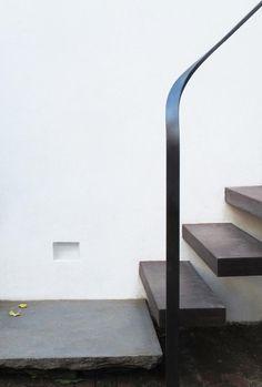 Floating wood stairs, metal ribbon handrail