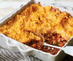 spoon scooping out baked layered vegetable and potato casserole