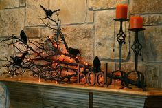 Halloween home decor, tree limb sprayed black with orange candles and bats fireplace mantle boo