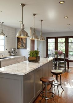 Grey cabinets (Dunn Edwards Legendary Grey sprayed on satin lacquer finish), marble counters, subway tile (full wall height), light pendants