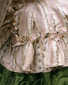 Detail of the ruffles, jacket, France, c. 1785. Striped Silk, lined with linen. Differentiated from the full-fledged Pierrot costume, the Pierrot as a shaped bodice flourished in that gasp of Rococo sensibility and extreme silhouette of about 1780 - 1790. The flared peplum extension of the jacket below the waist and asymmetrically around the back allows for the bulbous billowing skirt of the period. The bodice includes self-fabric ruffles, which would have embellished the skirt as well.