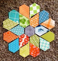 I sometimes wonder why this jewel flower isn't every bit as popular as the hexie flower. It makes such cool possibilities for fabric arrangements. (From Pitter Putter Stitch)