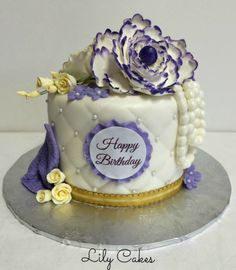 An elegant birthday cake with ombre rosettes in shades of purple