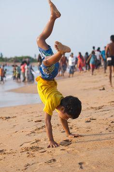 Boy cartwheeling in the beach