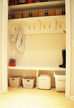 """A coat closet is converted into a """"mudroom"""" with open shelving, hooks, and lots of storage space for backpacks, coats, and pet supplies."""