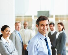 Smiling businessman with colleagues in the background Royalty Free Stock Photo