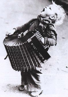 Boy singing and playing the accordion in the streets of Paris. A photo byHenri Manuel, 1930.