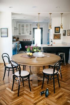 Herringbone floors appear throughout the home, including in the dining area, where black Thonet chairs from Design Within Reach sit around a wood pedestal table from Restoration Hardware.