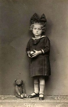 A girl and her teddy. The hugs bow on the girl's head reminds me of my grammie's girlhood photos.