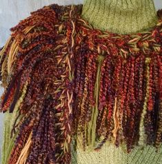 This scarf is ready to ship. It is multi-color emphasizing rust, teal, plum, lime, and wheat, as shown in picture. Total length is 73. The drop from the shoulder is 34 It is double fringed, measuring 7 and overlaid with another 5 to give it a beautiful dimension. Whether it is