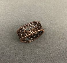 A copper wire woven mens ring. Antiqued and polished to bring out the weaves highlights. The ring is a size 11 (23 mm ).