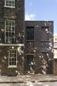 Chris Dyson Architects has added a soot-washed brick extension with a curved wall to a Georgian terraced house