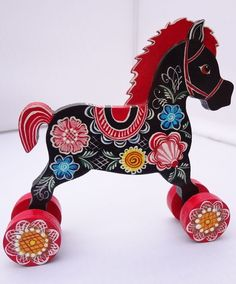 A wooden toy horse, handmade and decorated with Russian folk Gorodets painting