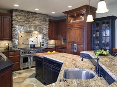 This kitchen has it all...slate flooring, a gorgeous stone-hooded range...rustic black distressed wood that adds just enough interest and edge against the warm walnut cabinetry. A really beautiful balance.
