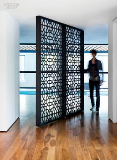 A custom screen in laser-cut, powder-coated steel pivots 360 degrees to provide access to the house's gym and indoor pool. Photography by Steve Tsai.