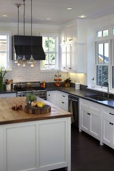 They could have had windows behind the range but chose to wall and tile it in. Like the two counters mixed. Beautiful kitchen design with white kitchen cabinets with honed black granite counter ... butcherblock island