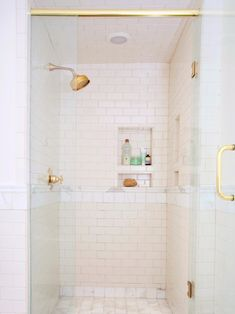A glass-enclosed shower was added in the space where a toilet once sat. To keep the feeling open and connected to the rest of the bath area, Green stuck with the same wall tiles used throughout the bathroom. A rain shower-style shower head made from 24 karats Venetian gold sprays triple the amount of water from the existing one.