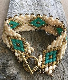 Southwestern themed single wrap design with beautiful turquoise and bronze diamonds outined with travertine colored superduo beads. This is a pretty piece. Looks good layered with other bracelets and/or bangles. Perfect for any occasion whether you are dressing up or just casually. Turn around time is usually one week. It does NOT include shipping time. If you need this piece quickly, please message me to make arrangements.