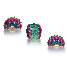 A SET OF RETRO MULTI-GEM JEWELLERY  Comprising a brooch of bombé design, the front set with graduated square-cut beryls, enhanced by a line of cabochon ruby collets, the sides set with lines of carved rubies and sapphires, to the diamond detail, a pair of ear clips en suite, mounted in gold, circa 1940.