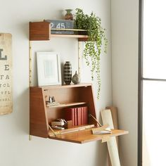 Simple, sophisticated storage. Inspired by American modern design, the Mid-Century Wall System mixes a warm walnut finish with retro metal hardware. Hang these shelves on rails as part of a modular system or simply fasten directly to the wall. A fold out desk doubles as a cabinet for extra storage and work space.