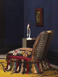 The slipper chair, covered in antique fabrics and trims, from Gina Bianco.   The 'S.A.M.' box side table is by Martin Szekely; the rug is by Fedora Design.    photograph by Pieter Estersohn