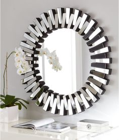 Like a modern sunburst, the Afina Modern Luxe Round Wall Mirror is sure to bring light to any room thanks to its round frame made up of mirrored glass rectangular pieces.