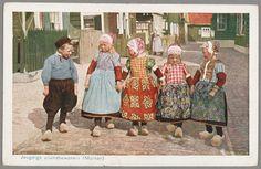 Meisje en vier jongens in Marker streekdracht. Links een jongen in boezeroen (soort overhemd) en broek, daarnaast een meisje en rechts daarvan drie jongens in rokkendracht. De jongens in rokkendracht zijn o.a. te herkennen aan hun geruite borstlap en gebloemde schort. 1910-1931 #NoordHolland #Marken