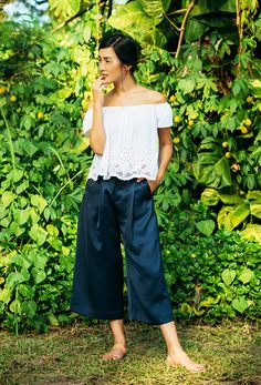 Nicole Warne of Gary Pepper Girl wears a white lace eyelet off-the-shoulder top, culottes, and nude slide sandals