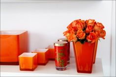 Create a wonderful vignette using different sizes and shapes of vases in one color.  Matching flowers is a nice touch. #orange  #vase