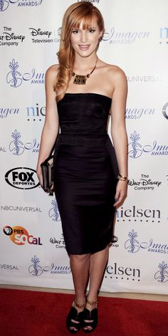 At the Imagen Awards, Bella Thorne elevated her black strapless Olima Atelier dress with key accessories: A statement Iossellianim necklace, gold bangles, Pierre Hardy bag and zippered Prada heels with gold accents.