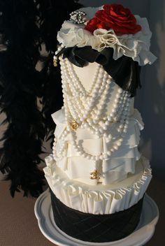 Chanel gâteau d'anniversaire inspiré - Ce gâteau inspiré Chanel comprend plusieurs des motifs Chanel Coco Chanel emblématiques y compris fleur-le favori Camillia, fabriqué à partir de pâte de sucre.  Brins de perles, Quiting noir et des tonnes de volants et plis tissu en couches et textures couvrent un gâteau à trois niveaux.