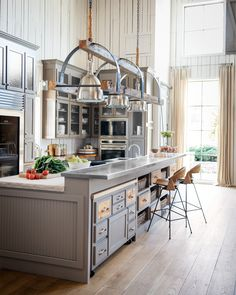 This kitchen adds a layer of refinement to the rustic home. An abundance of moody gray cabinetry, limestone countertops, and stainless steel appliances add luxe elements to the rough-hewn space.