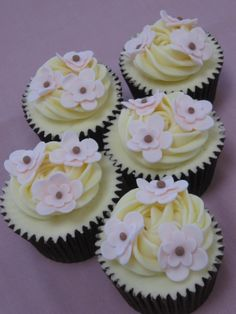 Vanilla cupcakes decorated with vanilla buttercream and sugar flowers.