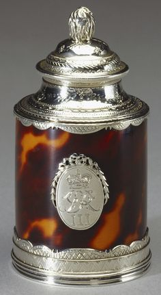 Pepper mill, c. 1770. A cylindrical tortoiseshell pepper mill with a silver lid, with a pinecone finial and tooled rim.