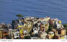 Typically colorful, cascading Cinque Terre houses, Italy - Cinque Terre is an area of five beautiful villages on the Italian Riviera. They are known for their picturesque houses, charming narrow streets, magnificent nature and the views. These lovely Ligurian gems are popular holiday destinations that offer truly unique Italian experience that should not be missed.
