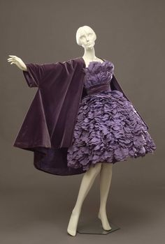 Short dress in lilac taffetas, composed by different curled trimmings to form a corolla. The wide cape in lilac velvet has a longer hemline on the back; Roberto Capucci (1930-), Rome, 1957. Collection...