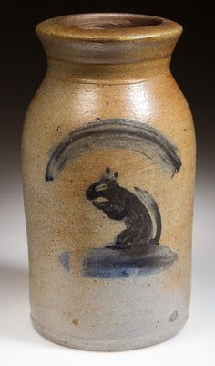 "FINE AND RARE THOMPSON POTTERY, MORGANTOWN, WEST VIRGINIA FOLK-ART-DECORATED STONEWARE DIMINUTIVE CANNING JAR.  Brushed cobalt decoration of a seated squirrel eating a nut below an arch device. Attributed to the Thompson Pottery (active c. 1810-1890), Morgantown, WV. Circa 1860-1870. 7 3/4"" H, 3 1/2"" D rim."