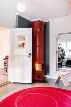 Ikean pyöreä matto toistaa punaiseksi maalatun pönttöuunin muotoa ja sävyä. Jyskin peilin edessä on Petrin tekemä Pari-jakkara, design Veera Sievänen. Pallovalaisin on hankittu Ikeasta.