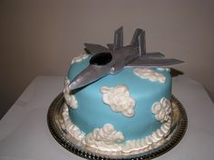 4 layer cake with alternating layers of chocolate and vanilla covered with marshmallow fondant and decorated with buttercream clouds. Fighter jet model made of gum paste and hand painted with silver shimmer to look metallic. Airplane Birthday Cakes, Camo Birthday, Airplane Party, Birthday Ideas, Fighter Jet Cake, Gun Cakes, Planes Cake, Book Cakes, Sweet Caroline
