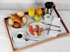 Breakfast tray laying on white bed