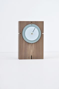 Introducing a surprising layout with colored discs as minutes and hour  hands on a wooden base.  The inner disc displays the minutes, the outer disc the hours. The clock  can be used standing horizontal and vertical or hanging on the wall.