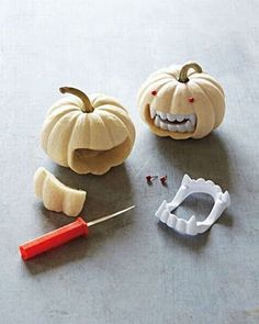 Holding vampire teeth closed, trace a line around them onto the pumpkin. Use a pumpkin saw to remove the area and enough of the inside for teeth to sit like in picture. Trim 2 red pushpins. Stick t...
