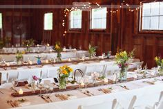 Family style tables set up at the wedding reception barn at the West Mountain Inn in Arlington, VT.  The bride's father milled the long wooden table runners and the bride used blue ball jars as vases for her wildflower centerpieces!