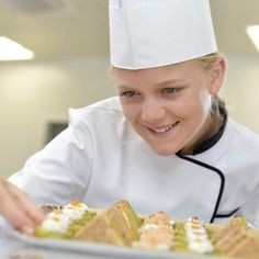 Young caterer preparing a tray of appetizers.