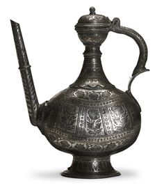 Bidri ewer, of zinc alloy and decorated with inlaid silver. Piriform ewer with flat sides rising from a circular stand, lotus petal collar at the base of the neck. [...]   Horniman Museum and Gardens   CC0