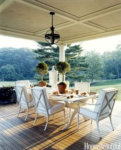 Designer Alex Papachristidis chose classic shapes and, rather than bright hues, neutral colors, which work well for fall in this outdoor dining room