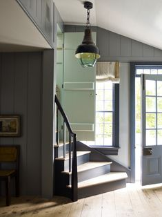 FARMHOUSE – INTERIOR – vintage early american farmhouse showcases raised panel walls, barn wood floor, exposed beamed ceiling, and a simple style for moulding and trim, like in this farmhouse foyer by steven gambrel interiors.