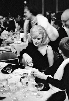 """A melancholy Monroe toys with her ever-present glass of champagne, at an Actor's Studio benefit at New York's Roseland, 1961.  This was MM's first public appearance after her hospitalizations for emotional issues earlier in the year--including a nightmarish four days confined at the Payne Whitney Clinic.  She was now much thinner than she'd been for several years, but the quick weight loss, combined with the traumas of the Miller divorce, the hospitals and the failure of """"The Misfits"""" had…"""