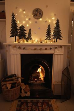 hearth mantel: evergreen trees, moon, ceramic house lanterns, string lights, garland, ...