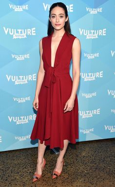 Emmy Rossum looks so good in a Paule Ka red tea length dress with a bow detail and peach pointed toe pumps to the Vulture Festival.